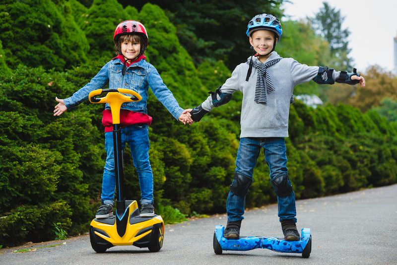 2 Kids riding electric hoverboards in the street